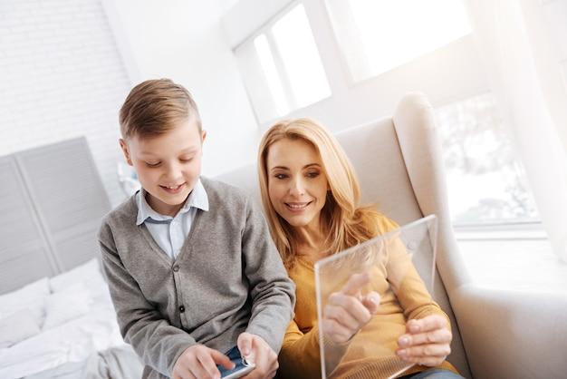 Laatste ontwikkelingen. leuke positieve gelukkige vrouw die samen met haar zoon zit en een tablet vasthoudt tijdens het gebruik van moderne technologie