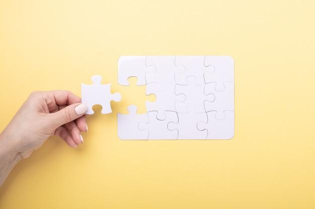 Laatste stuk puzzel in de hand witte puzzel