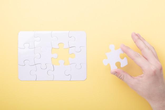 Laatste stukje puzzel in de hand witte puzzel concept succes van zaken gele achtergrond bovenaanzicht