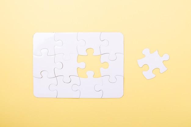 Laatste stukje puzzel witte puzzel concept succes van zaken gele achtergrond bovenaanzicht