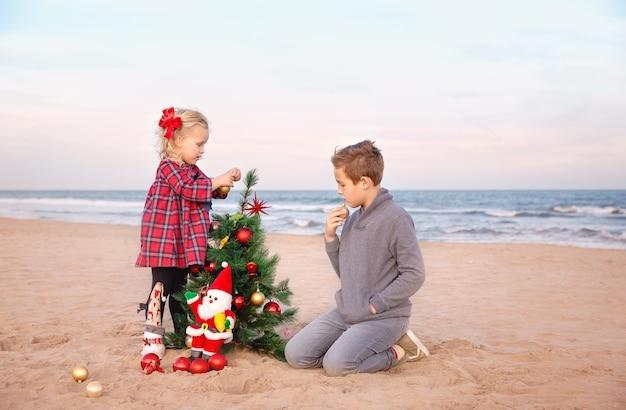 Laatste voorbereidingen voor familiefeest op het strand om kerst te vieren. meisje dat met broer de boom verfraait