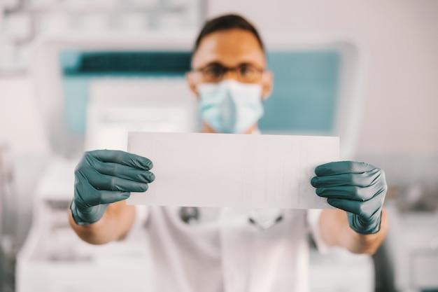 Lab-assistent die zich in het laboratorium bevindt en papier met resultaten vasthoudt. coronavirus uitbraak concept.