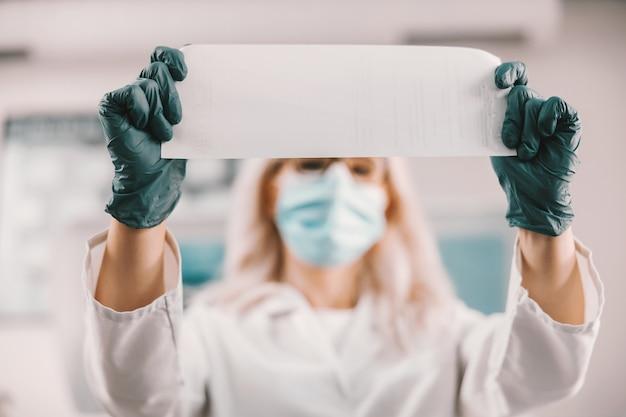Lab assistent houdt papier met resultaten. coronavirus-uitbraak concept.