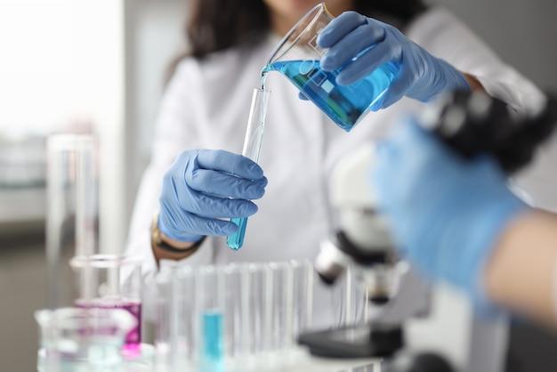 Lab-technicus met handschoenen giet chemische stof in reageerbuis. wetenschappelijk onderzoek in chemie