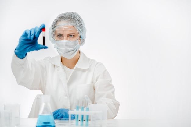 Lab werknemer in uniform met masker en handschoenen kijken naar bloed op witte achtergrond