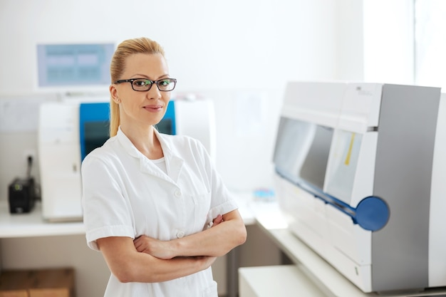 Labassistent met bril permanent in lab met gekruiste armen