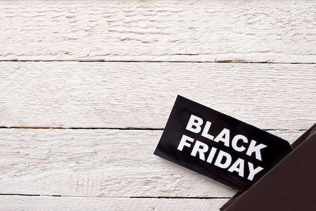 Label black friday op witte houten achtergrond met ruimte voor tekst.