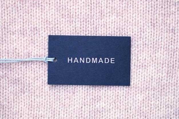 Label met inscriptie handgemaakt op gebreide textuur