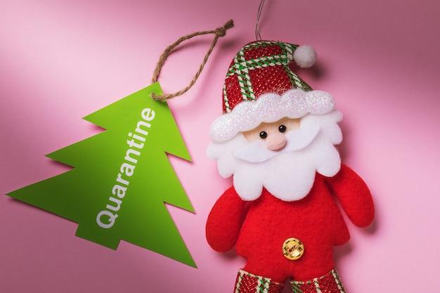 Label met tekst en speelgoed santa claus op een roze achtergrondconcept op het gebied van quarantaine voor de nieuwjaarsvakantie