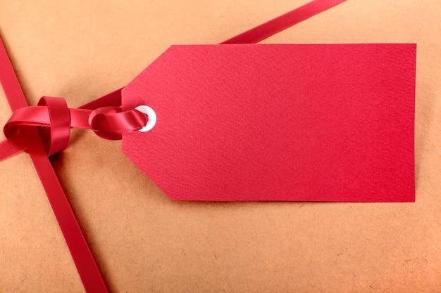 Label van de close-up het rode gift en lint, de bruine achtergrond van het pakket verpakkende document, exemplaarruimte.