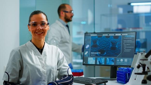 Laboratorium arts kijken camera glimlachend in modern uitgerust lab. multi-etnisch team dat virusevolutie onderzoekt met behulp van hightech- en scheikundige hulpmiddelen voor wetenschappelijk onderzoek, vaccinontwikkeling.