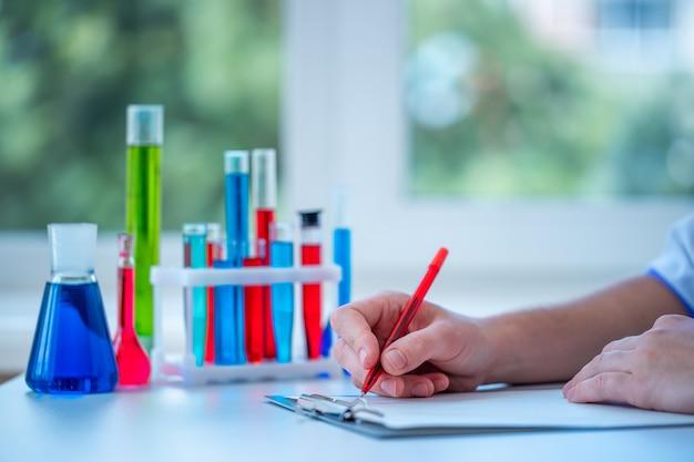 Laboratoriumassistent verricht klinisch laboratoriumonderzoek en schrijft het resultaat van het onderzoek in klembord. geneeskunde, apotheek en cosmetologie concept. wetenschappelijk glaswerk voor test