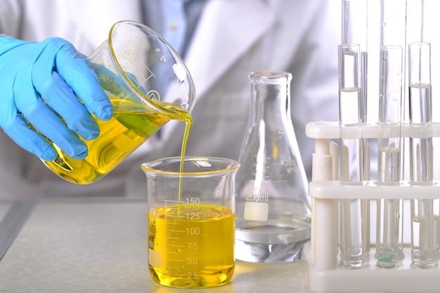 Laboratoriumbeker in analistenhand in plastic handschoen