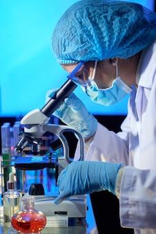 Laboratoriummedewerker die door microscoop kijkt