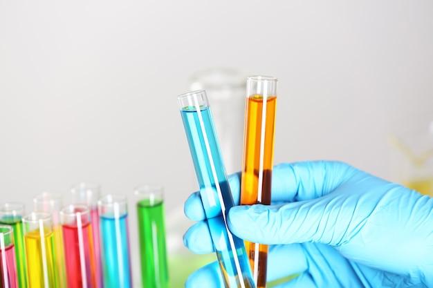 Laboratoriummedewerker die reageerbuisjes met kleurrijke vloeistoffen vasthoudt, close-up