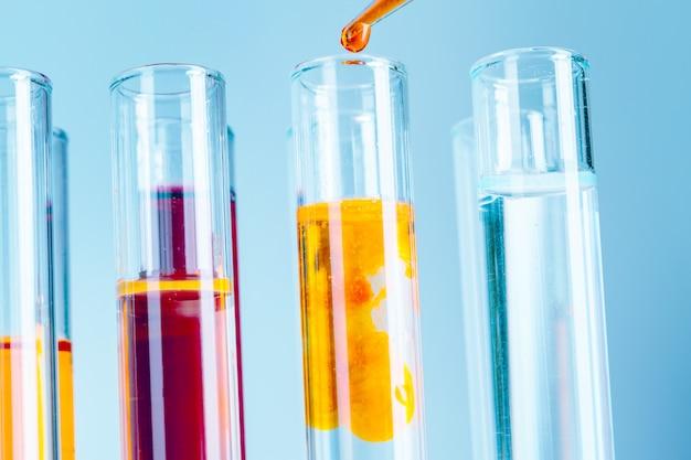 Laboratoriumreageerbuizen met rode en gele vloeistoffen op lichtblauwe achtergrond