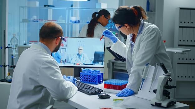 Laboratoriumtechnici praten over videogesprek met professionele chemicus-arts die vaccinreacties uitlegt