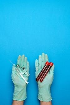 Laboratoriumtechnicus die rubberhandschoenen draagt die een ampul met geneeskunde houden