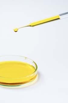 Laboratoriumtest laboratorium druppelaar met gele vloeistoftest in petrischaal