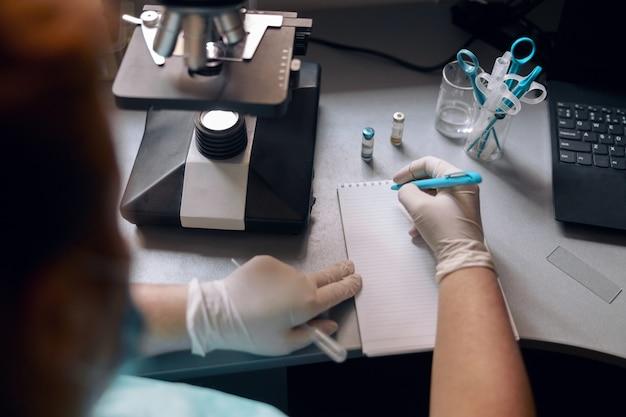 Labtechneut in latexhandschoenen schrijft markeringen in notitieboekje bij microscoop aan bureau