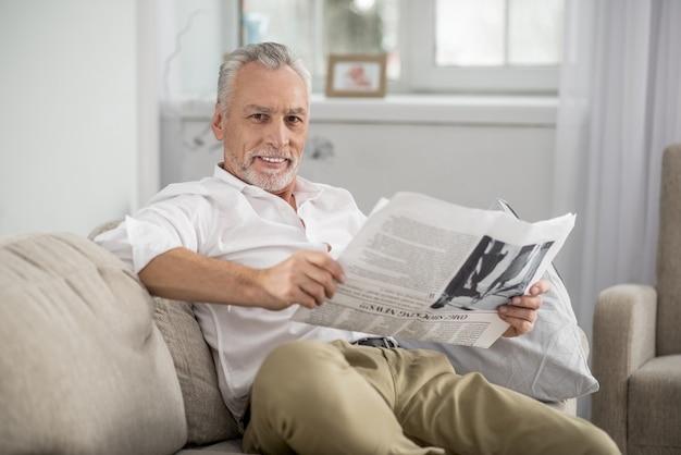 Lach altijd. vrolijke man die een glimlach op zijn gezicht houdt en de krant vasthoudt terwijl hij recht in de camera kijkt