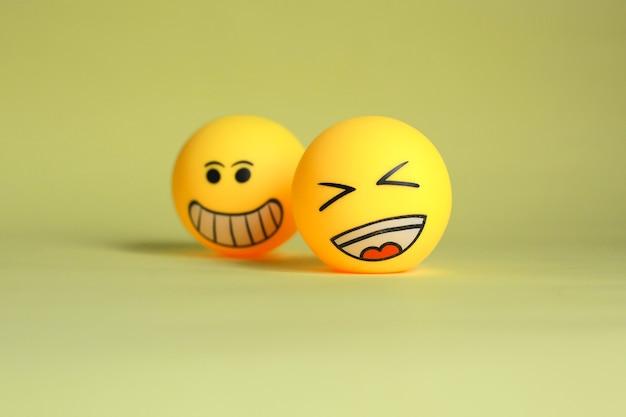 Lach emoticon en wazige smiley emoticon geïsoleerd op gele achtergrond