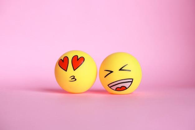 Lach en liefde emoticon met mond kussen geïsoleerd op roze achtergrond