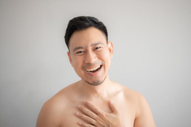 Lach gezicht van aziatische man in topless portret geïsoleerd op een grijze achtergrond.