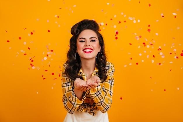 Lachen europese dame poseren met confetti. grappig pinupmeisje dat zich op gele achtergrond met oprechte glimlach bevindt.