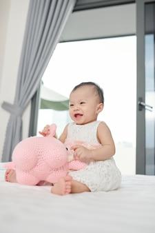 Lachen gelukkig babymeisje zittend op bed en spelen met speelgoed