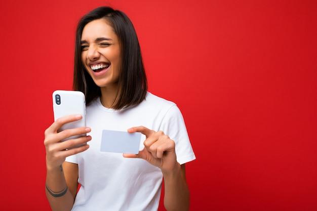Lachen gelukkig jonge vrouw, gekleed in alledaagse kleren geïsoleerd op achtergrond met telefoon en creditcard