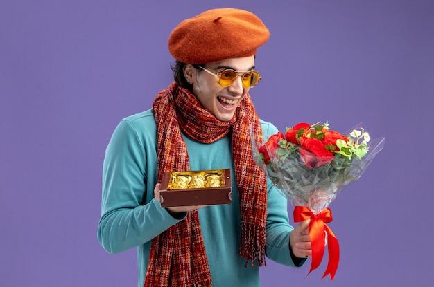 Lachen jonge kerel op valentijnsdag dragen hoed met sjaal en bril houden en kijken naar boeket met doos snoep geïsoleerd op blauwe achtergrond