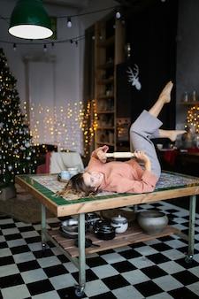 Lachen lachende leuke vrouw in huiskleren met plezier in de keuken versierd met slingers