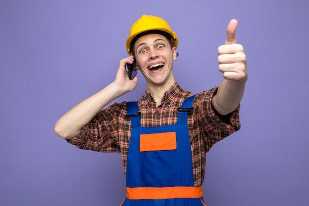 Lachen met duim omhoog jonge mannelijke bouwer die uniform draagt, spreekt op de telefoon