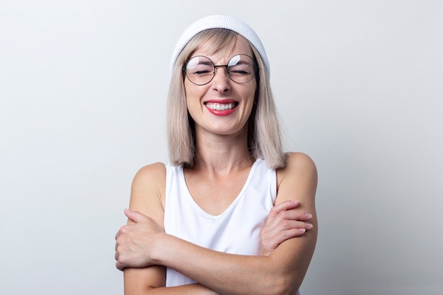 Lachen met gesloten ogen jonge vrouw houdt haar armen gekruist in een wit t-shirt op een lichte achtergrond. Premium Foto