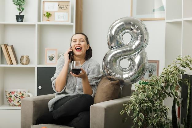 Lachen met gesloten ogen mooie vrouw op gelukkige vrouwendag met glas wijn spreekt over wijn zittend op een fauteuil in de woonkamer