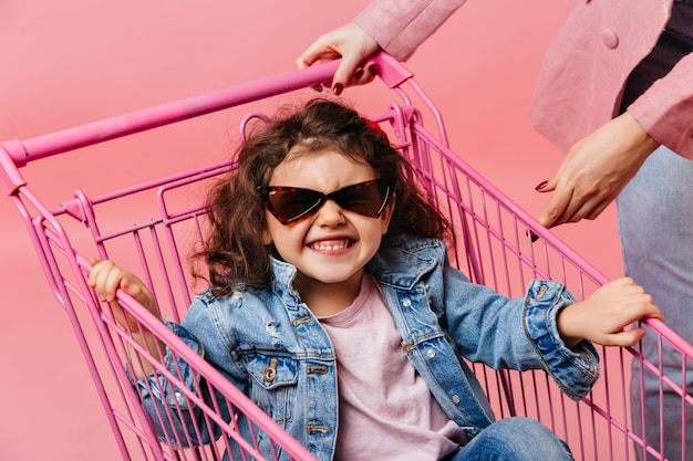 Lachen preteen jongen zit in winkelwagen. studio shot van krullend kind in denim jasje en zonnebril.