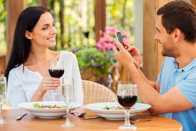 Lachen voor de camera! knappe jongeman die foto's maakt van haar mooie vriendin met smartphone terwijl hij samen in het openluchtrestaurant ontspant