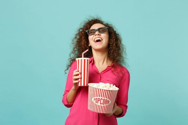 Lachend afrikaans meisje in 3d-imax-bril die naar film kijkt, houd popcornkopje frisdrank geïsoleerd op blauwe turkooizen achtergrond in de studio. mensen emoties in de bioscoop, lifestyle concept. bespotten kopie ruimte.