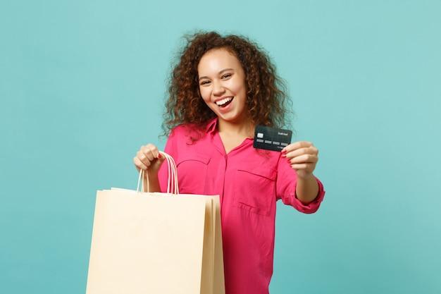 Lachend afrikaans meisje in vrijetijdskleding houdt pakkettas met aankopen vast na het winkelen met creditcard geïsoleerd op blauwe turkooizen achtergrond. mensen oprechte emoties levensstijl concept. bespotten kopie ruimte.