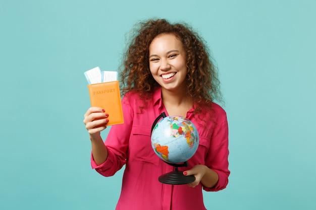 Lachend afrikaans meisje in vrijetijdskleding met earth wereldbol, paspoort instapkaart ticket, geïsoleerd op blauwe turkooizen achtergrond. mensen oprechte emoties, lifestyle concept. bespotten kopie ruimte.