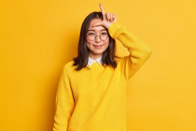 Lachend aziatisch meisje maakt verliezer gebaar over voorhoofd kijkt tevreden zegt vriend dat je vorm bent kwijtgeraakt l brief met vingers maakt grapjes over team draagt ronde bril en trui