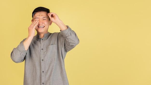 Lachend. aziatische jonge man portret op gele muur. knap mannelijk model in casual stijl. concept van menselijke emoties, gezichtsuitdrukking, jeugd, verkoop, advertentie.