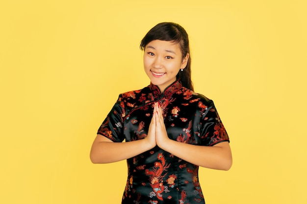 Lachend, bedankt schattig. gelukkig chinees nieuwjaar. aziatisch jong meisje portret op gele achtergrond. vrouwelijk model in traditionele kleding ziet er gelukkig uit. viering, menselijke emoties. copyspace.