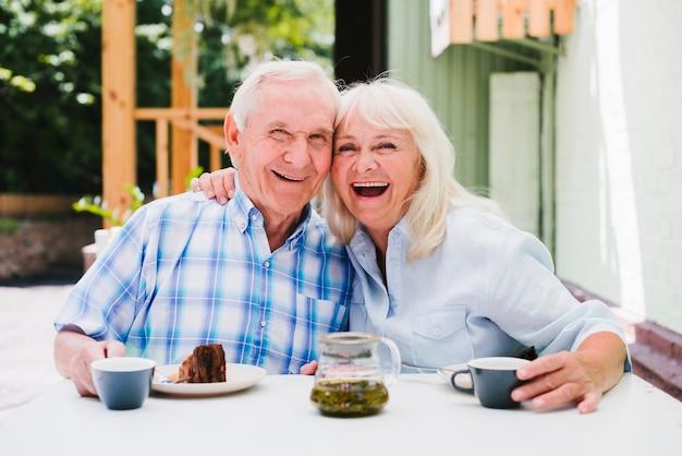 Lachend bejaard echtpaar dat cake eet en thee drinkt