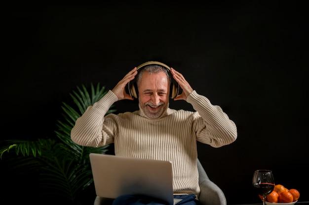 Lachend bejaard mannetje dat op hoofdtelefoon zet
