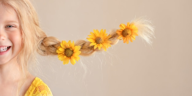 Lachend blond kaukasisch meisje met gele madeliefjebloemen in vlechten die grappig aan de zijkant uitsteken half gezicht close-up portret