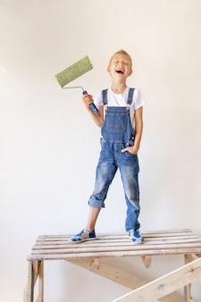 Lachend blond kind staat op een bouwladder in een appartement met witte muren