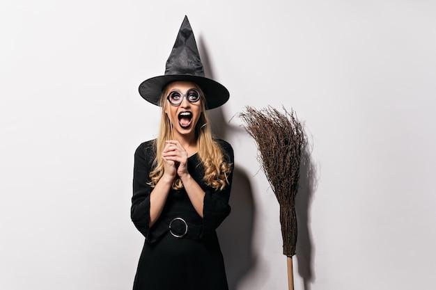 Lachend blond meisje genieten van maskerade in halloween. goedgehumeurde heks poseren in zwarte hoed.