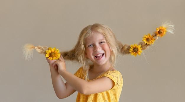 Lachend blond meisje met bloemen in haar vlechten